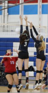 Erin Alonso and Lauren Tierney jump for a block