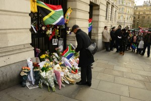 Offerings to Mandela's memory pile up underneath a South African flag.