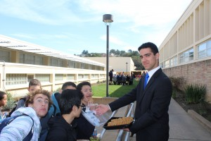 Senior class president candidate Omid Afshar serving cookies to potential voters before they head to the voting booths.