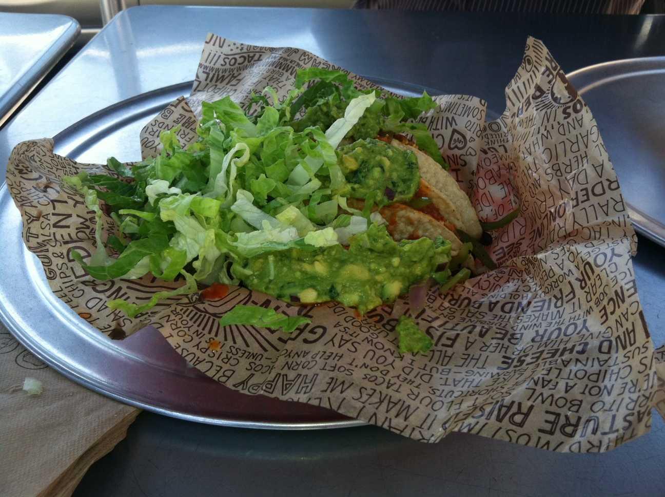 Three tacos hiding under guacamole