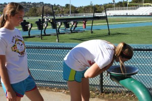 Without water bottles, freshmen Sydney Adair (left) and Isabel Peate (right) make a trip to the water fountain to stay hydrated at girls' basketball conditioning.