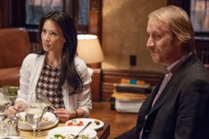Joan Watson (Lucy Liu, left) has dinner with Mycroft Holmes (Rhys Ifans, right) as Sherlock Holmes leaves to work on the case.