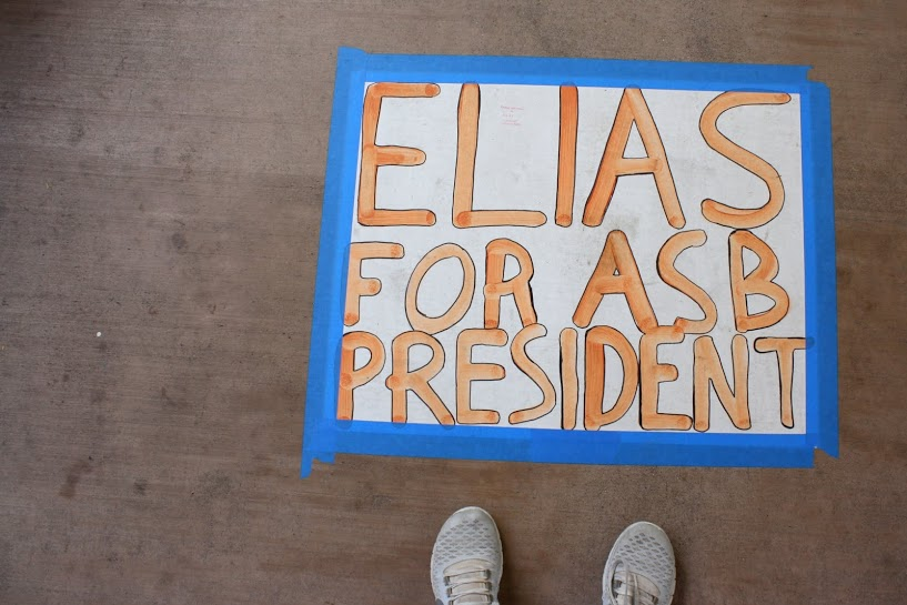 Along the main stairs, students look down to find posters promoting junior Elias Sebti.