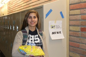 Junior Elise Dimick poses excitedly next to one of her campaign flyers. She and Elias Sebti ran for ASB President where the whole school voted for them.